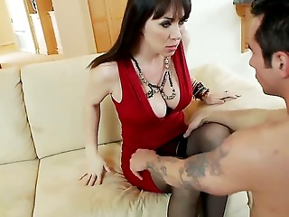 hot and busty dark haired milf in steamy red dress rayveness gets her shaved taco licked on the couch in her living room by a randy young dark haired man joey brass and enjoys